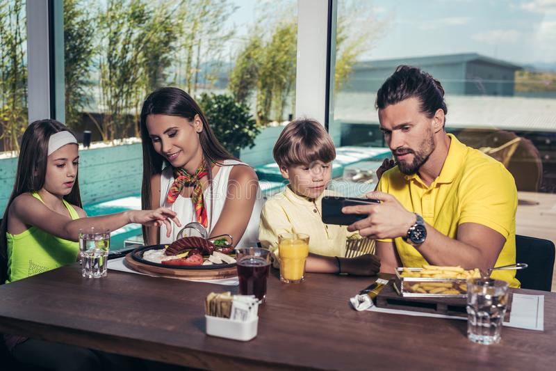 Father and mother with children enjoying meal in restaurant. royalty free stock photography