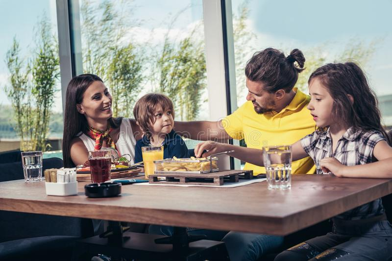Father and mother with children enjoying meal in restaurant. stock images