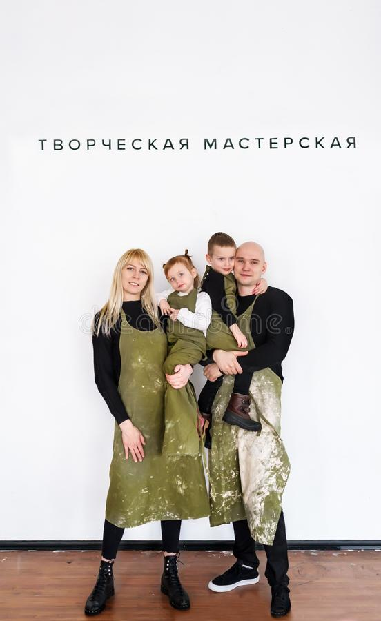 The father, mother and children in green aprons. Family portrait in a creative workshop. stock photography