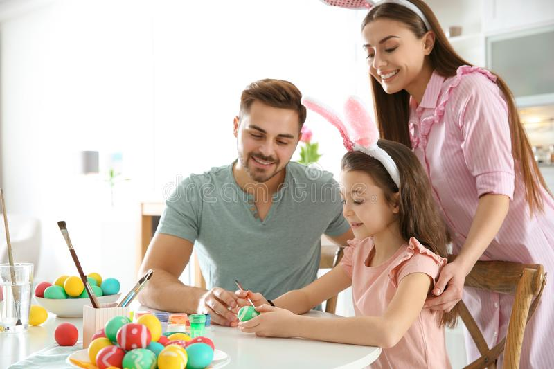 Father, mother and daughter painting Easter eggs in kitchen royalty free stock photography
