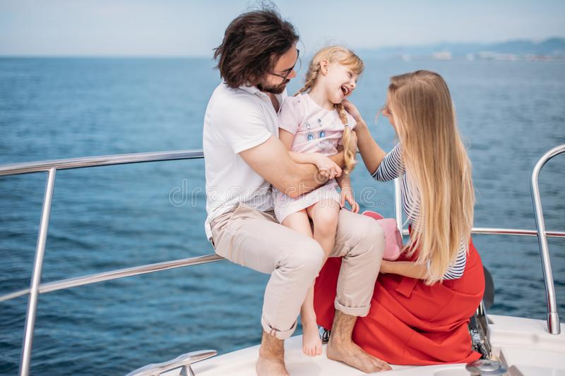 Father, mother and daughter sailing on yacht at the sea royalty free stock images