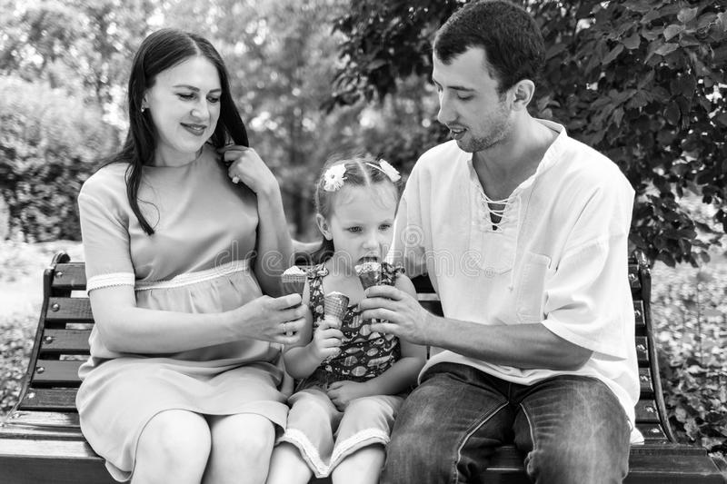 Father, mother and daughter sit on bench and eat ice cream. A man shares his ice cream with a girl. Woman pregnant. Father, mother and daughter sit on bench and royalty free stock image