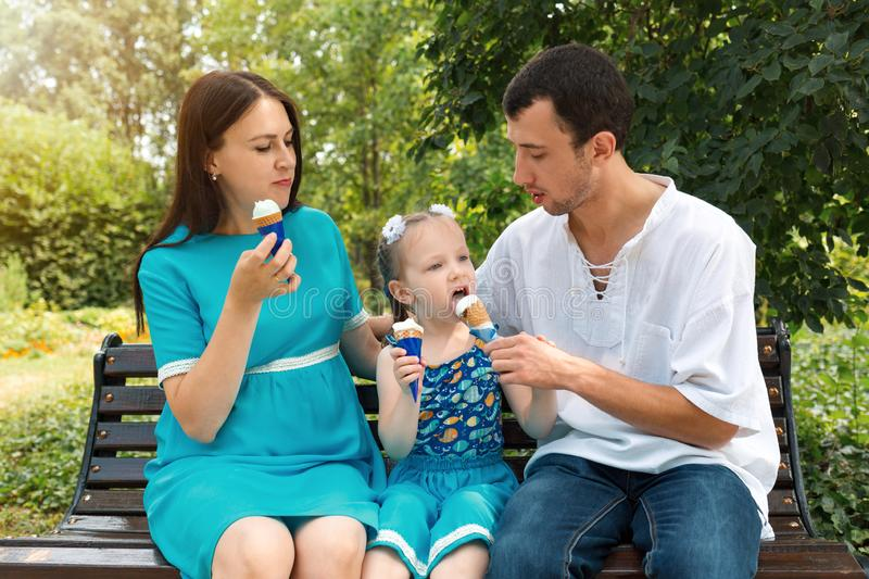 Father, mother and daughter sit on bench and eat ice cream. A man shares his ice cream with a girl. Woman pregnant. Father, mother and daughter sit on bench and royalty free stock photography