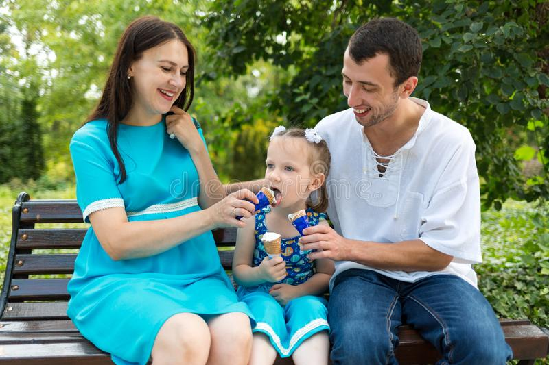 Father, mother and daughter sit on bench and eat ice cream. A pregnant woman shares her ice cream with a girl. Father, mother and daughter sit on bench and eat stock photos