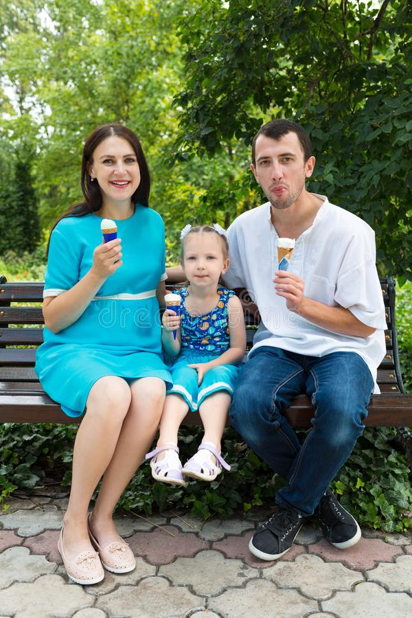 Father, mother and daughter sit on bench and eat ice cream. Woman pregnant. Vertically framed shot royalty free stock photography