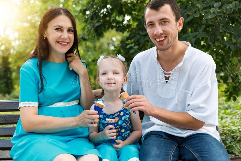 Father, mother and daughter sit on bench and eat ice cream. Woman pregnant. Horizontally framed shot stock photos