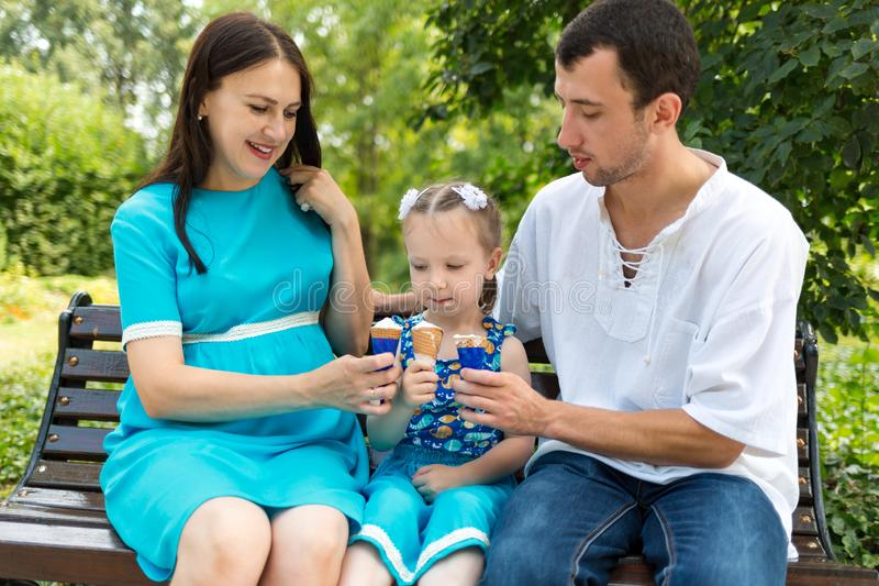 Father, mother and daughter sit on bench and eat ice cream. Woman pregnant. Horizontally framed shot royalty free stock photo