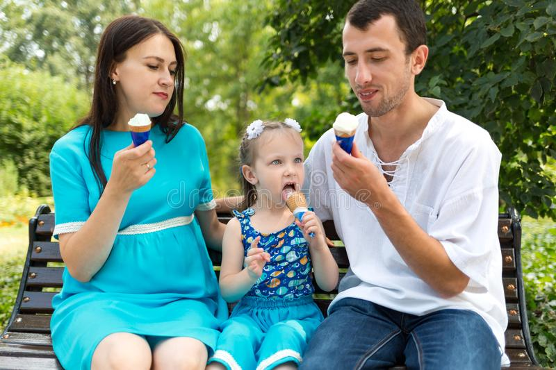 Father, mother and daughter sit on bench and eat ice cream. Woman pregnant. Horizontally framed shot royalty free stock photography