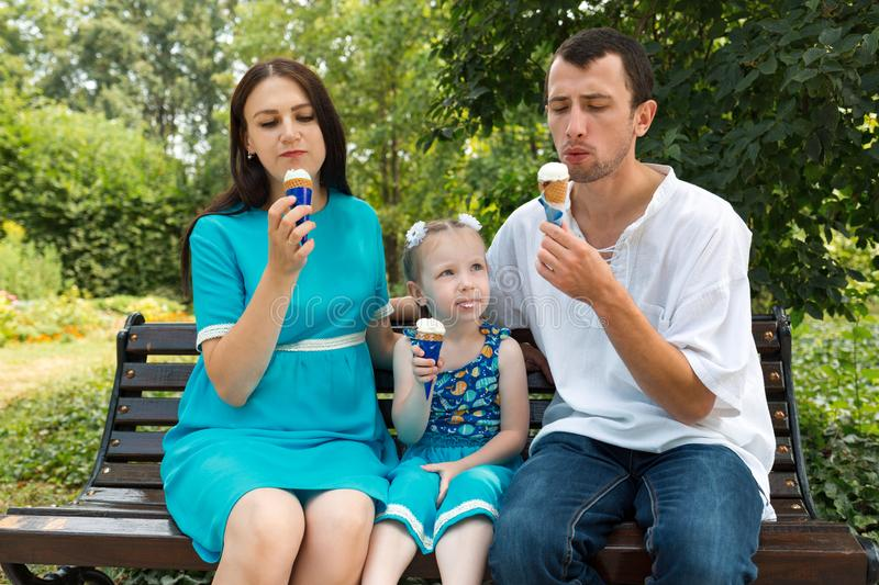 Father, mother and daughter sit on bench and eat ice cream. Woman pregnant. Horizontally framed shot stock image