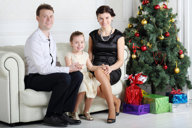 Father And Mother With Daughter Sit Near Christmas Tree Royalty Free Stock Image