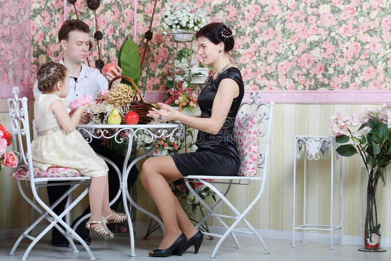 Father, mother and daughter sit at table with fruits. And beautiful basket in retro interior royalty free stock images