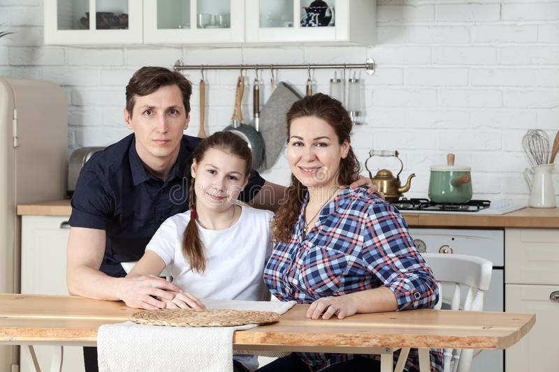 Father, mother with daughter sitting at table in kitchen together, portrait royalty free stock photos