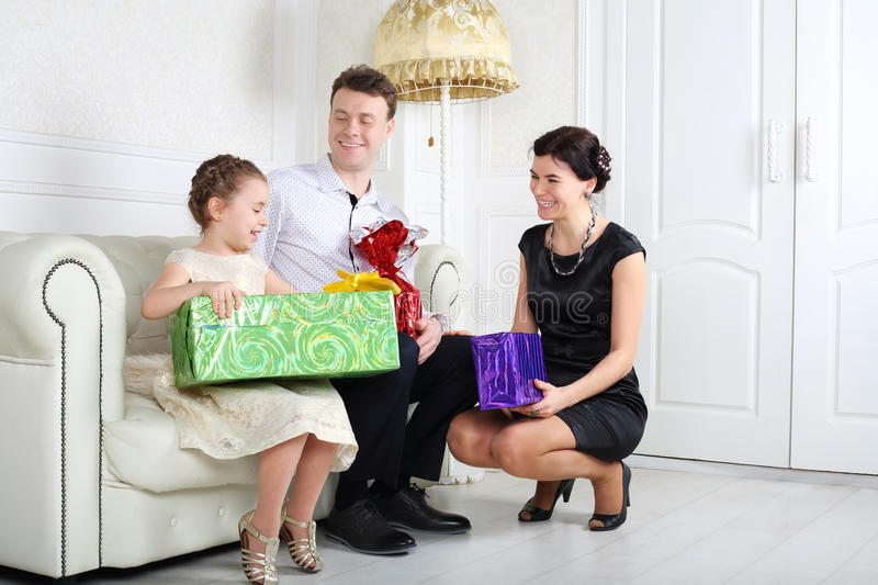 Father and mother give gifts to little daughter at sofa royalty free stock images