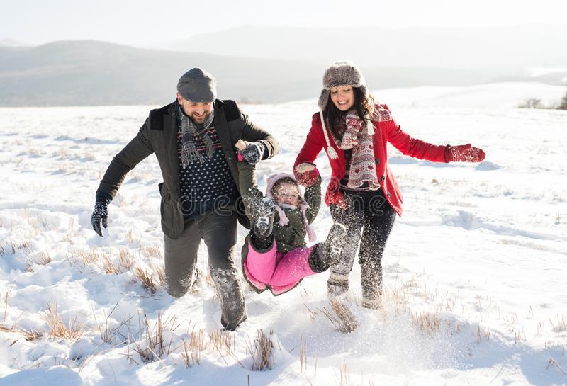 Father and mother with their daughter on a walk, winter nature. stock photography
