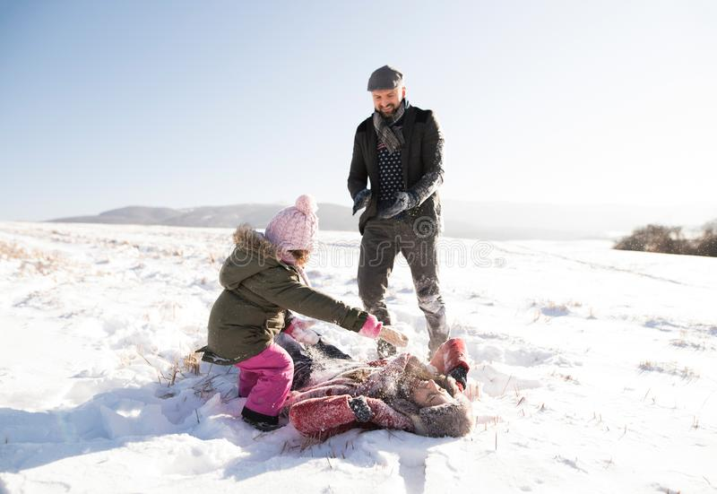 Father, mother and their daughter having fun in winter nature. stock images
