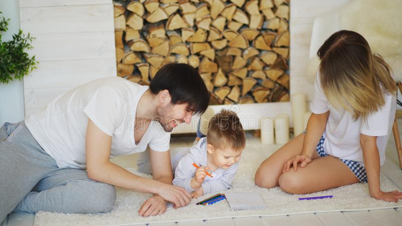 Father and mother helping their child draw picture in their living room. Father and mother helping their child to do draw picture in their living room at home stock image