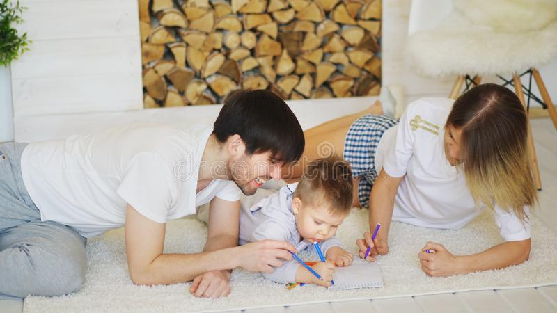 Father and mother helping their child draw picture in their living room. Father and mother helping their child to do draw picture in their living room at home royalty free stock image