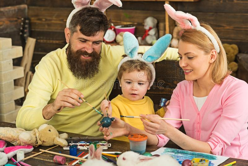 Father, mother and her child enjoy painting Easter eggs. royalty free stock photos