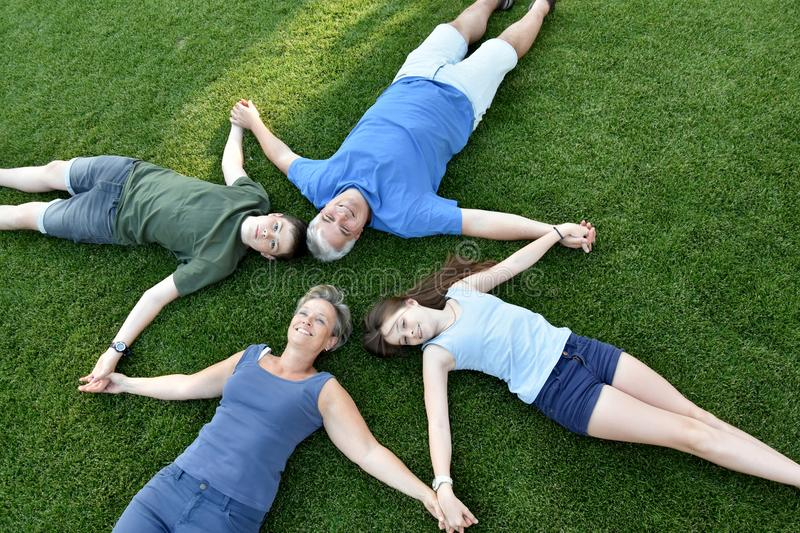 Family, father, mother, son and daughter lying in the meadow royalty free stock photos