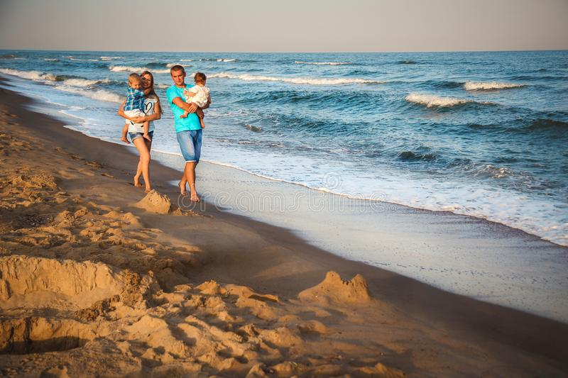 Father, mother and kids walking along the beach, near the ocean, happy lifestyle family concept royalty free stock photos
