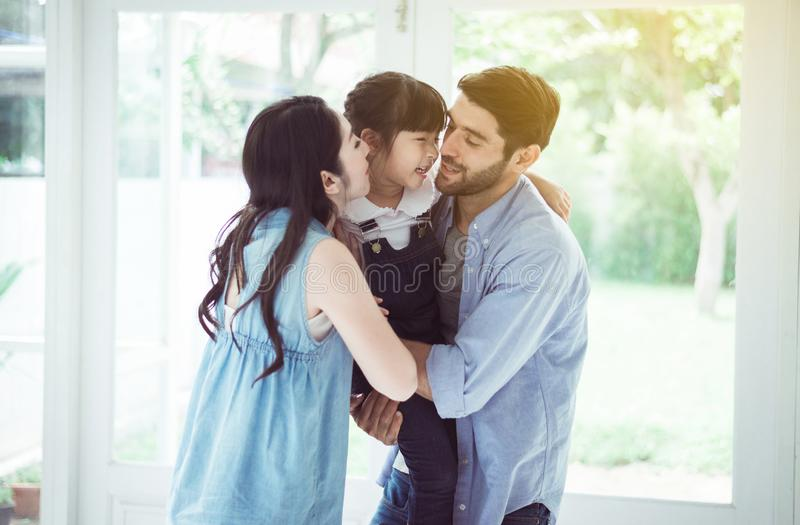 Father and mother kiss cheek daughter child girl playing,Laughing and funny together at home,Happy loving family royalty free stock images