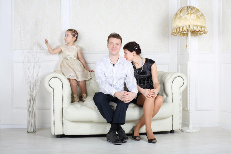Father, mother and little cute daughter sit at sofa. Father, mother and little cute daughter sit at white sofa in light room royalty free stock images
