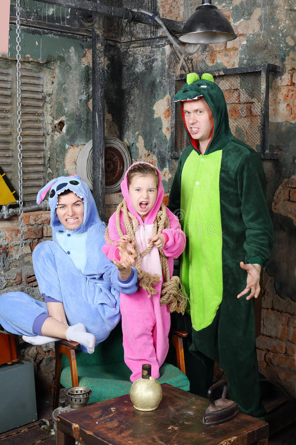 Father, mother and little daughter in costumes of dragons. Father, mother and little daughter in colorful costumes of dragons growl and scare in very old room royalty free stock photography