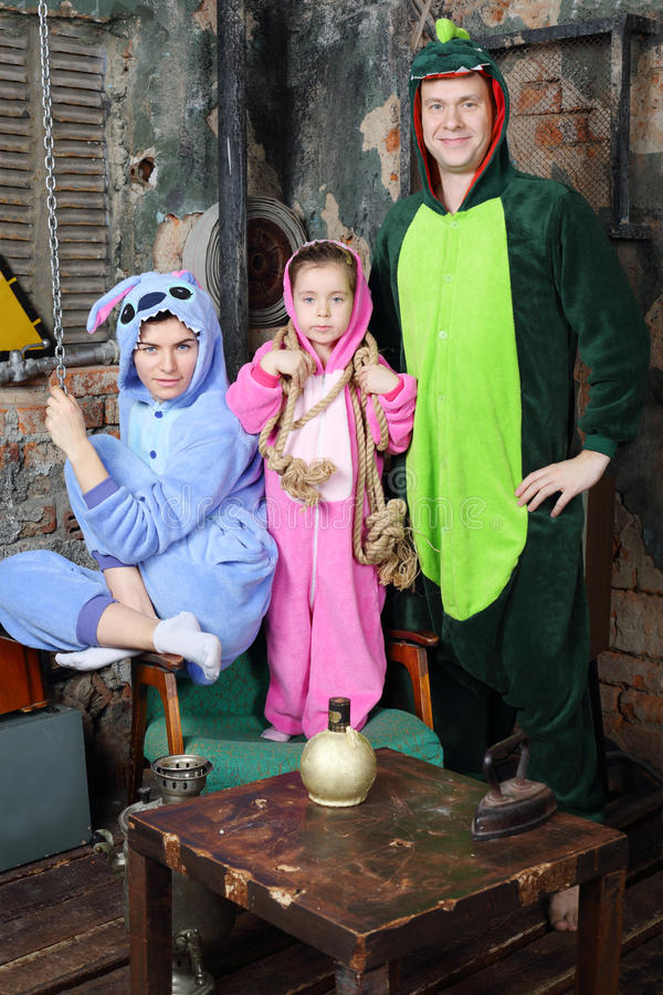 Father, mother and little daughter in costumes of dragons. Father, mother and little daughter in colorful costumes of dragons pose in very old room royalty free stock photo