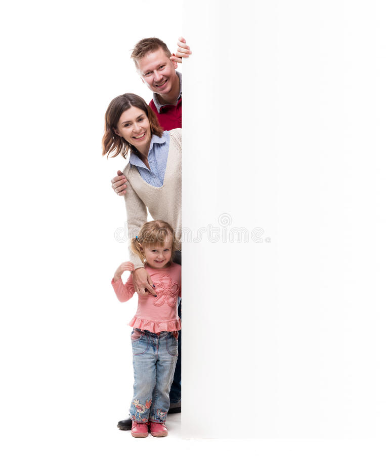 Father, mother and little daughter peek out from behind empty blank. Isolated on white background royalty free stock images