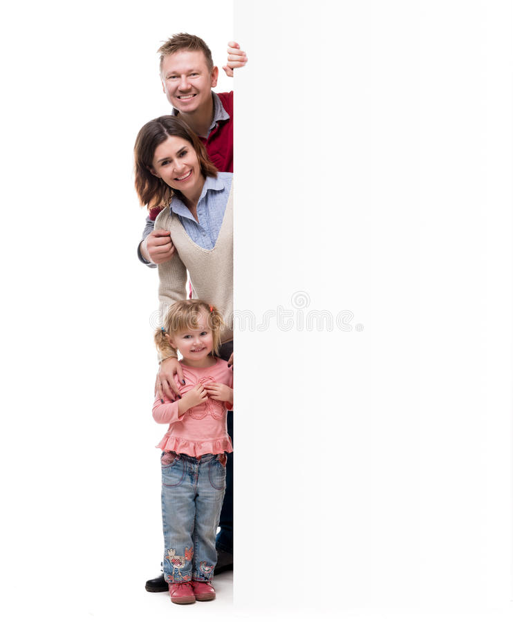 Father, mother and little daughter peek out from behind empty blank. On white background royalty free stock images