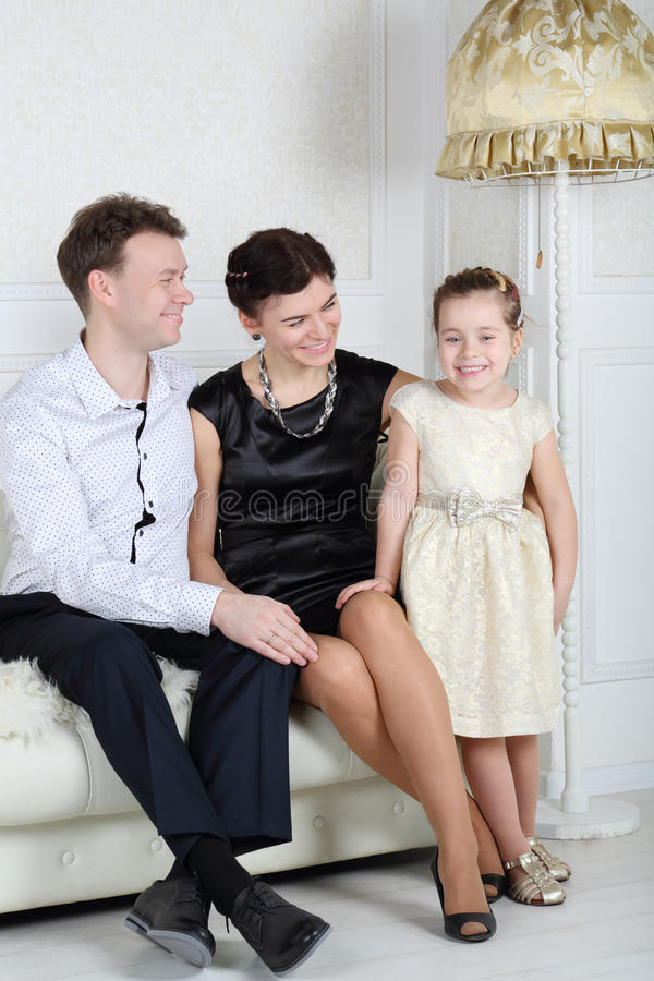 Father and mother look at little cute daughter. In light room royalty free stock images