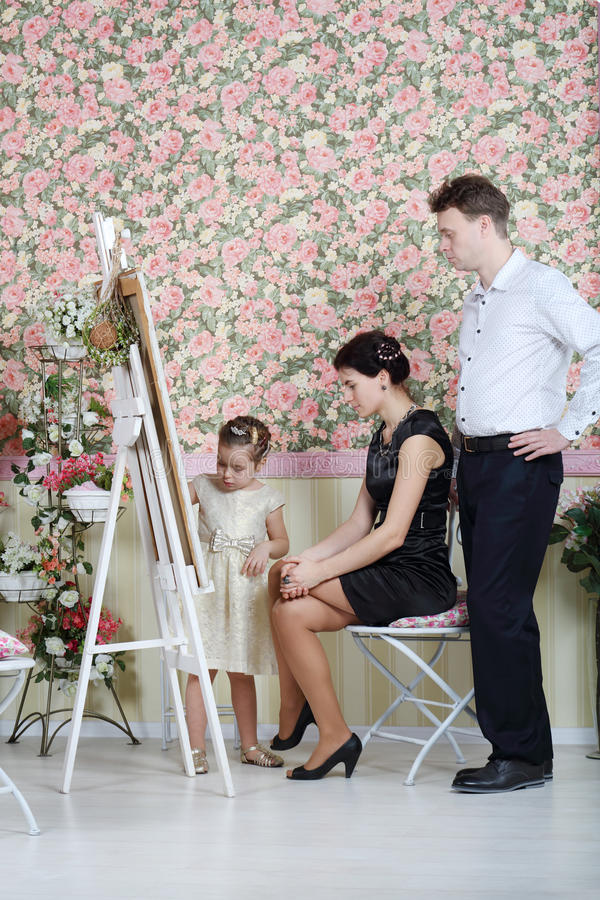 Father and mother look at their painting daughter. In beautiful retro interior stock photos