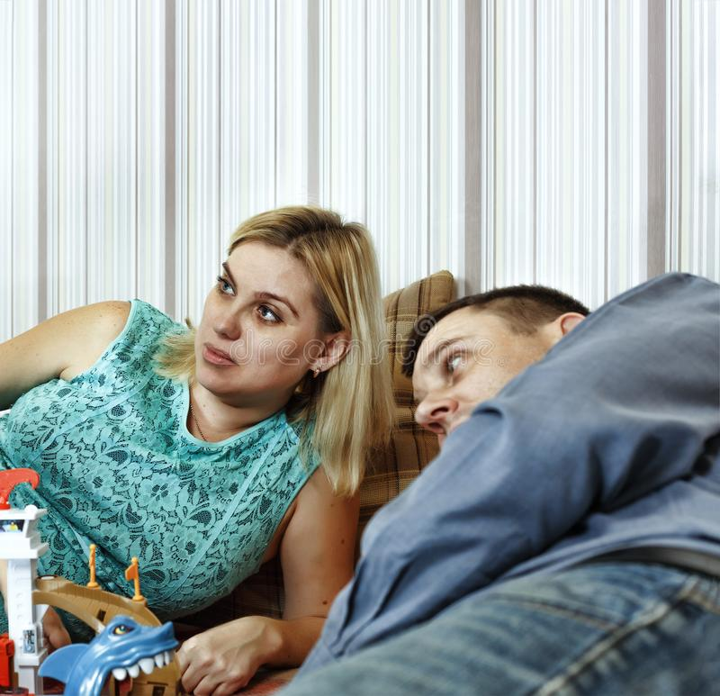 Father and mother play with their little son on the couch at home royalty free stock photography