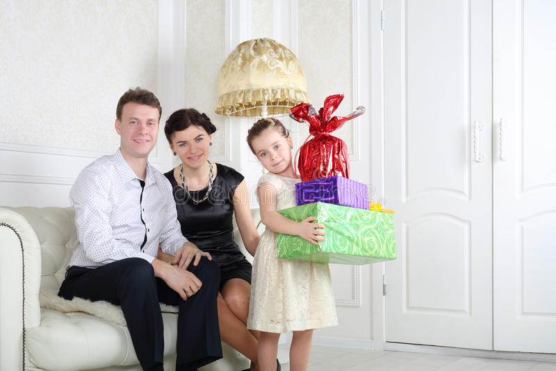 Father and mother sit at sofa and daughter with gifts royalty free stock photo