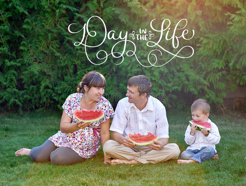 Father, mother and son eating watermelon sitting on the grass and text Day in the life. Calligraphy lettering vintage stock photo