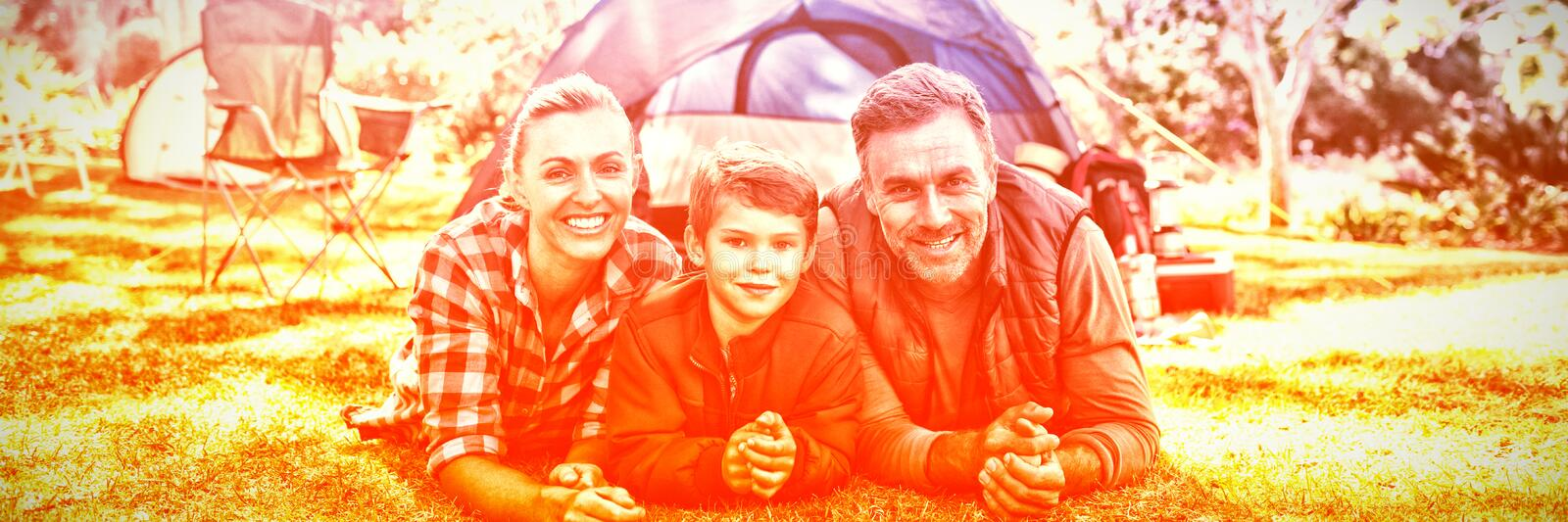 Father mother and son lying outside the tent at campsite stock photo