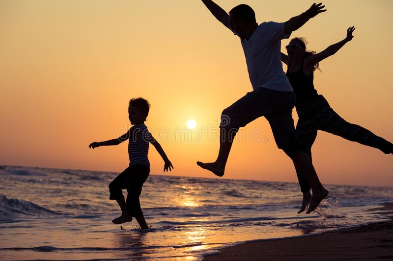 Father mother and son playing on the beach at the sunset time. stock image