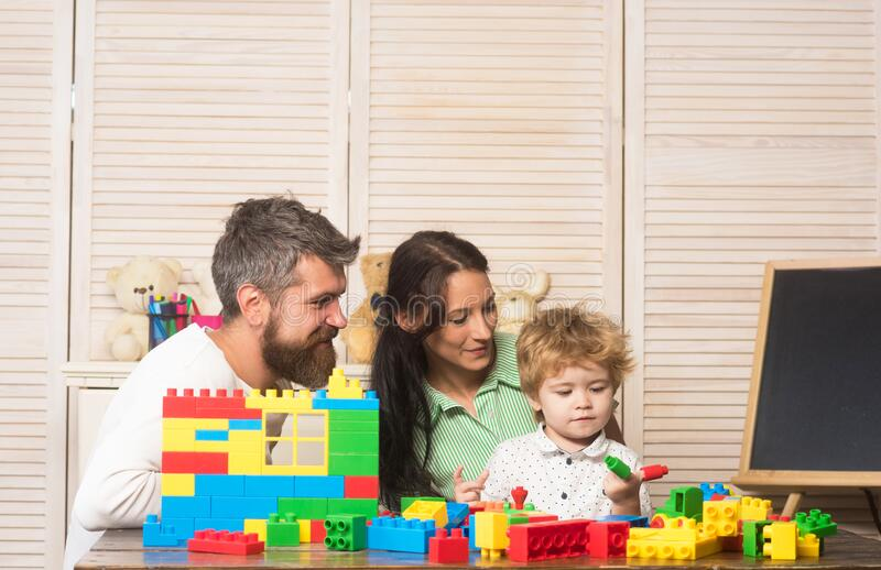 Father, mother and son in playroom on light wooden background. stock photography