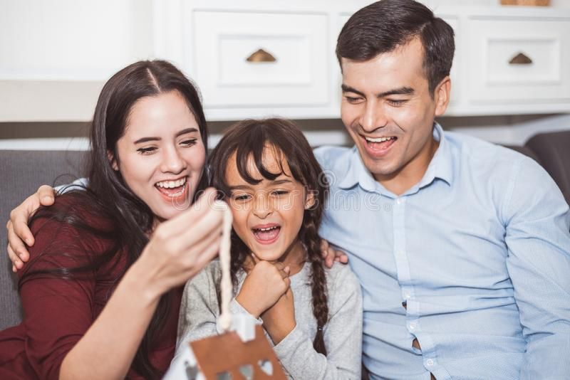 Father and mother surprise their daughter by gift or new toy. Parents and children are happy together in home on sofa in living royalty free stock image