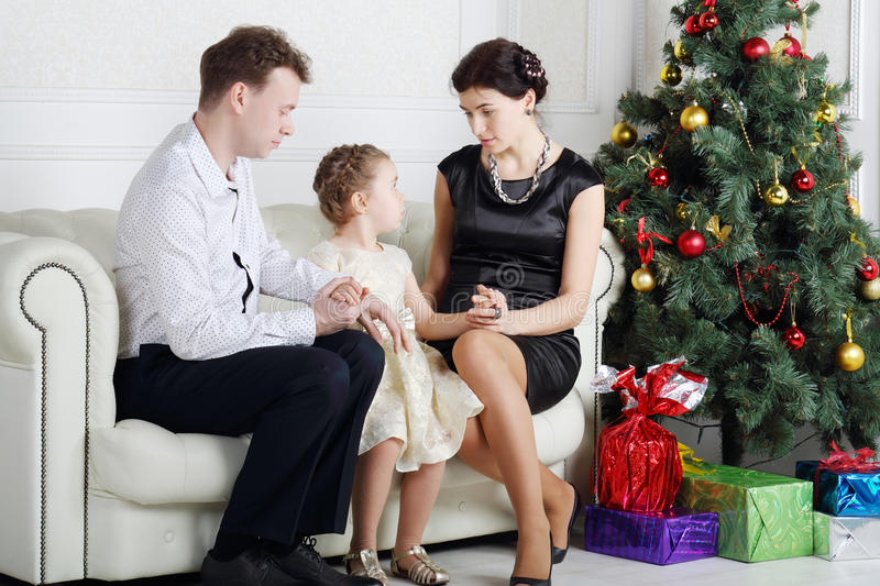 Father and mother talk with daughter on sofa near Christmas tree. In light room stock image