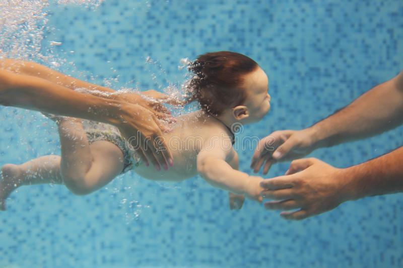 Father and mother teaching small child swimming underwater in the pool royalty free stock photo
