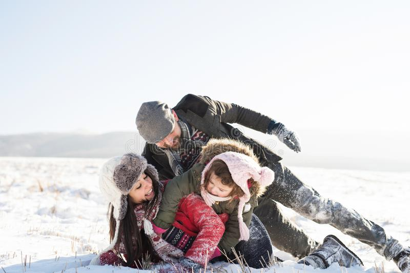 Father, mother and their daughter having fun in winter nature. stock image