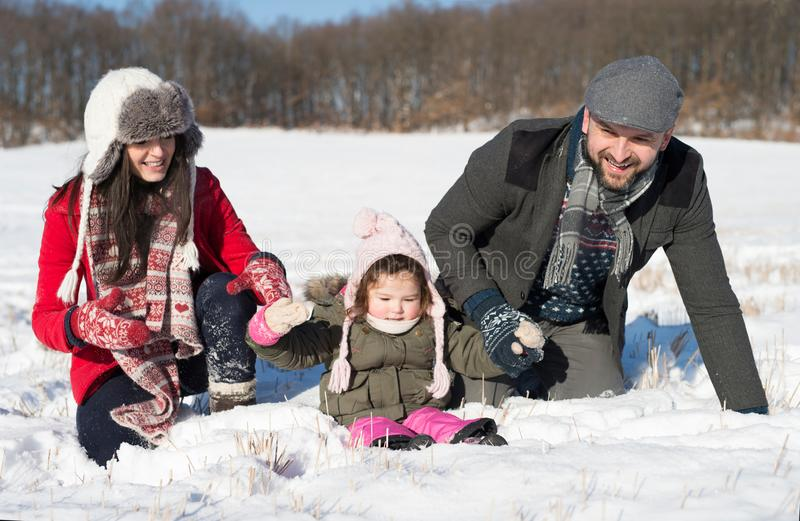 Father, mother and their daughter having fun in winter nature. stock photo