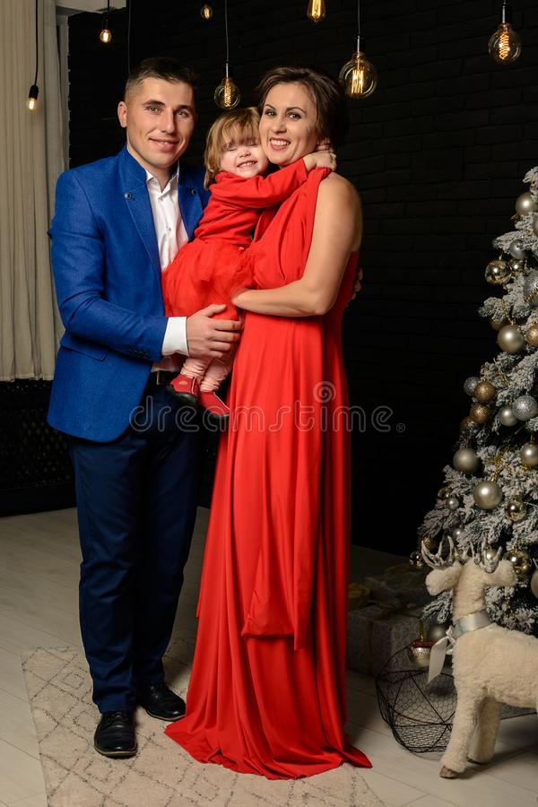 Father with mother and their daughter standing next to a Christmas tree mom with daughter in red dresses stock image
