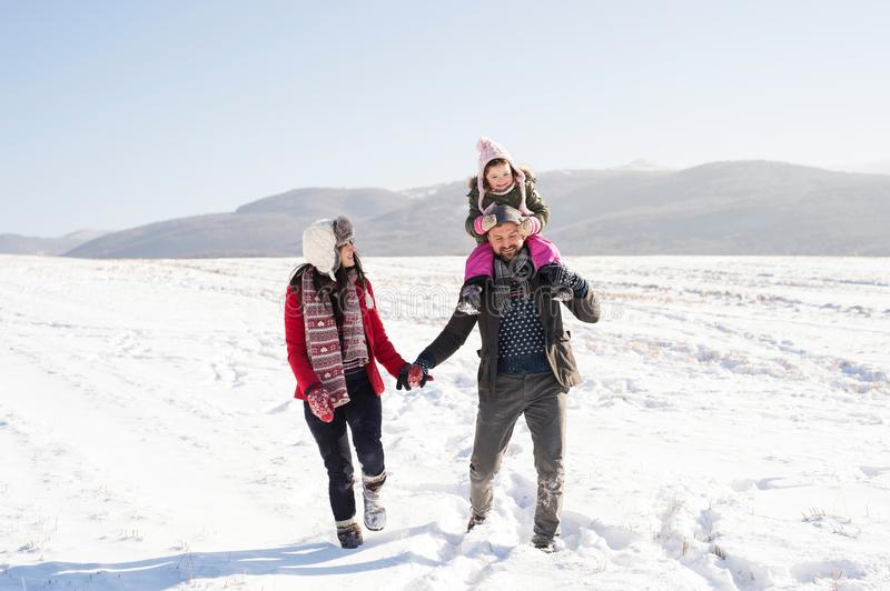 Father and mother with their daughter on a walk, winter nature. royalty free stock images
