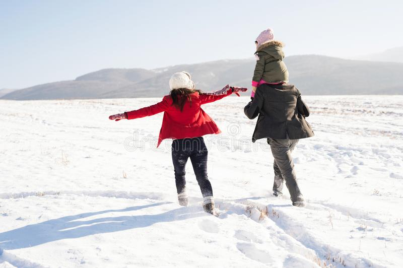 Father and mother with their daughter on a walk, winter nature. stock images