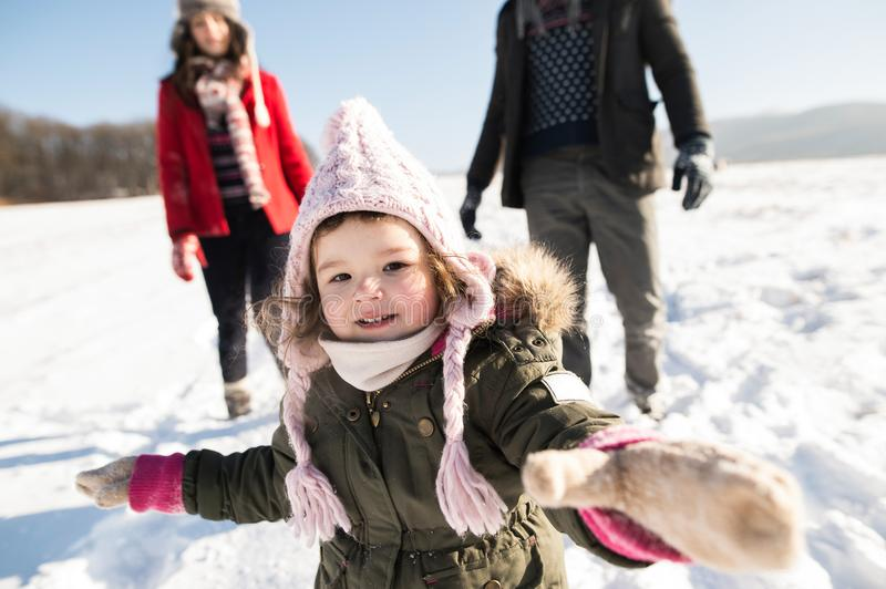 Father and mother with their daughter on a walk, winter nature. stock photos