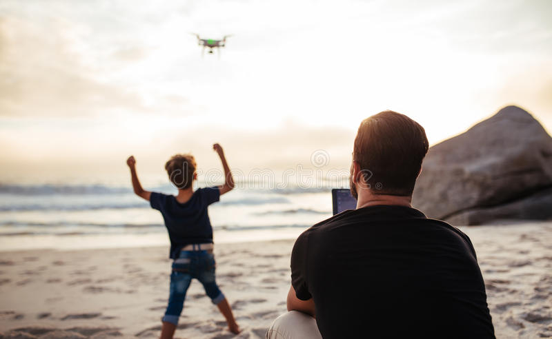 Father operating drone at beach and son cheering royalty free stock photo