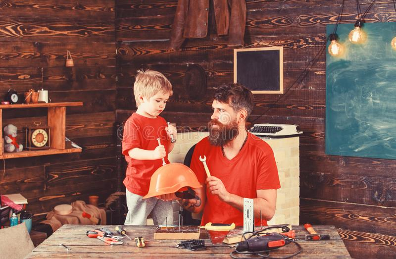 Father, parent with beard holds helmet teaching son safety in school workshop. Boy, child cheerful holds bolts or screws royalty free stock photography