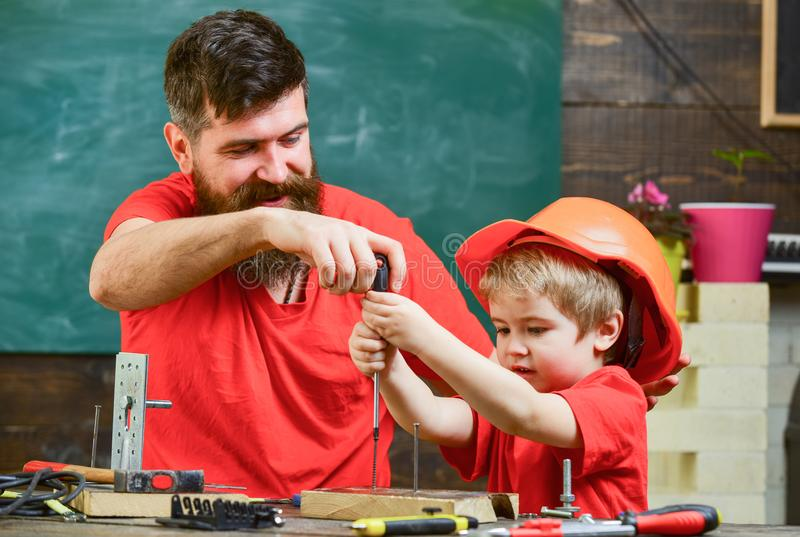 Father, parent with beard teaching little son to use tool screwdriver. Teamwork and assistance concept. Boy, child busy stock photos